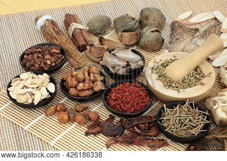 Chinese herbs and spice used in alternative herbal medicine with mortar and pestle on bamboo. Natural health care concept.