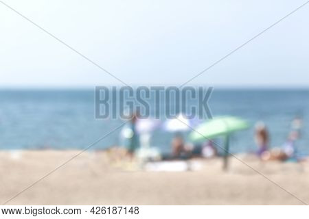 Summer Holiday Theme Blur Background. Blurred Background Of Sun Umbrellas On The Sea Beach. Abstract
