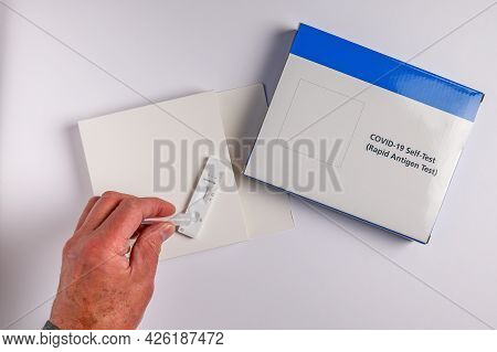 Coronavirus Covid-19 Lateral Flow Self Test Kit With Male Hand On White Background Rapid Antigen Tes
