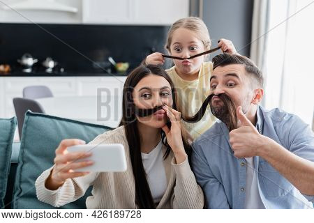 Woman Taking Selfie With Family Having Fun While Imitating Mustache With Her Hair