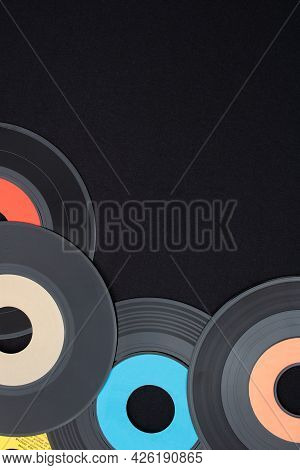 Multi Colored 7 Inch Single Vinyl Records On A Black Background Placed On Bottom Left Corner With Em