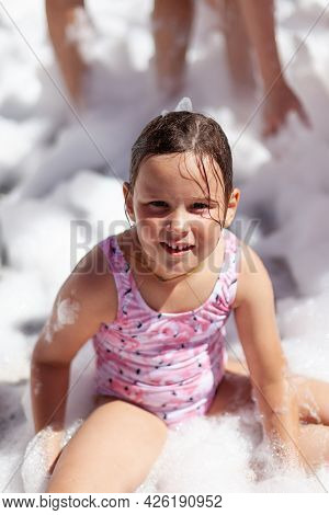 Caucasian Girl In A Pink Swimsuit Is Sitting In The Foam By The Pool At A Foam Party And Having A Go