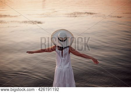 A Relaxed Woman Enjoys The Sun, Freedom And Life On A Beautiful Beach At Sunset. The Concept Of Vaca