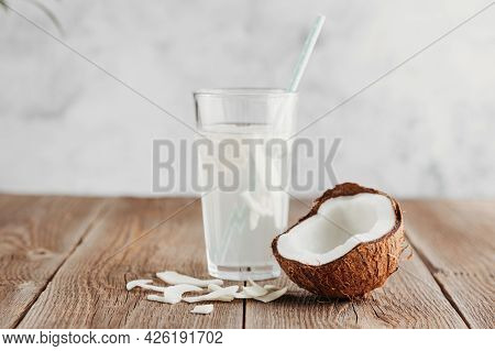 A Glass Of Fresh Organic Coconut Water, Milk On A Wooden Table And A Ripe Half Of A Coconut Nearby.
