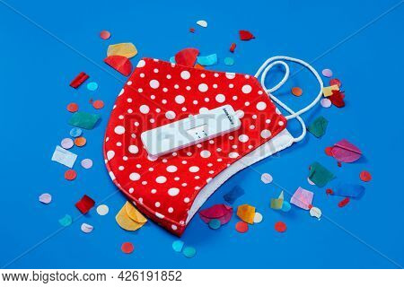 a covid-19 antigen diagnostic test device, a red face mask patterned with white dots and some confetti on a blue background, as a safe party set