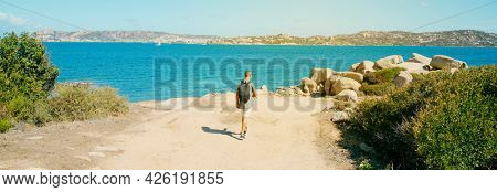 a young man, carrying a backpack, walks by the coast of the Mediterranean sea in Sardinia, Italy, with La Maddalena island in the background, in a panoramic format to use as web banner or header