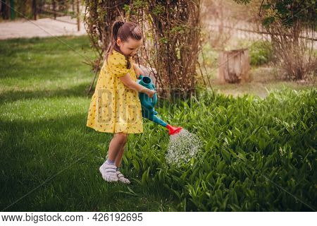 Charming Six-year-old Girl In A Yellow Dress Watering Lilies Of The Valley From A Blue Watering Can,