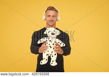 Happy Childish Middle-aged Man Listen To Music In Headphones Holding Dalmatian Toy Dog Yellow Backgr