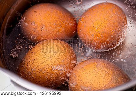 Four Brown Chicken Eggs Are Cooked In An Iron Pot With Boiling Water.