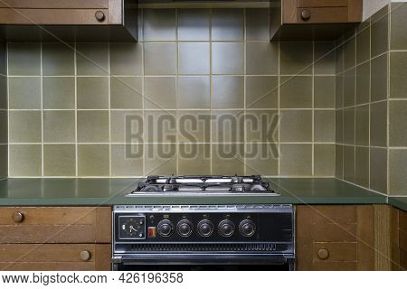 Interior Of A Old Retro Vintage Kitchen With Antique Oven With Brown Wooden Cabinets, Green Old Scho