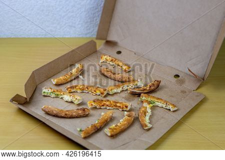 Pizza Crusts In A Greasy Box On A Home Table. Leftover Pieces Of Pizza. High-calorie Food