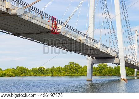 Unrecognizable Industrial Climber Work On A Cable-stayed Bridge. Working In Height Above The River.
