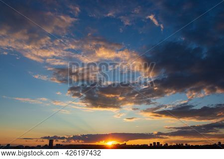 Bright Orange Rays Of The Setting Sun Against The Backdrop Of Magnificent Clouds And Sky