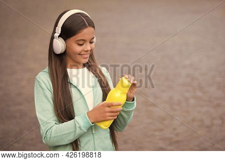 Active And Healthy Kid Drink Water. Child With Juice Bottle In Earphones. Back To School. Health Car