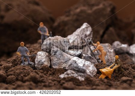 Mining Of Cobalt. Renewable Energy Concept. Miniature Worker Mining Metal Zinc And Silver. Mining Bu