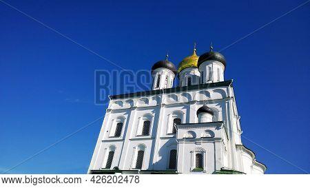 Trinity Cathedral, Pskov, Russia. Blue Sky Background. Pskov Kremlin. Ancient Fortress. Golden Dome.