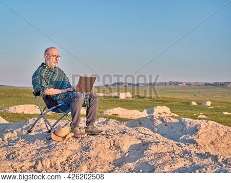 Senior man in Mexican poncho is sitting on a folding chair and working on laptop in the middle of nowhere, early morning in the badlands of Pawnee National Grassland in Colorado