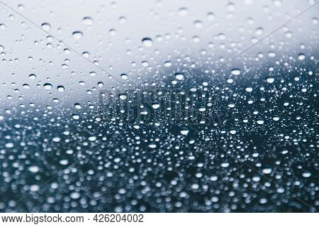 Close Up Of Rain Drops On The Windshield, Front Window Of A Car On A Blue Gray Background Of Dark Sk