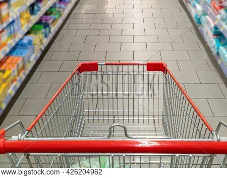 Supermarket Aisle With Empty Red Shopping Cart.