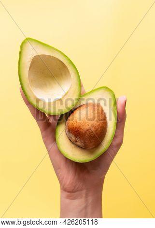 Sliced Avocado Fruit In Female Hands. Avocado. Avocado Fruit On A Yellow Background.