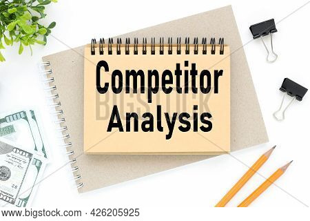 Competitor Analysis Concept. Text On White Notepad Paper. On A White Photo With Torn Paper
