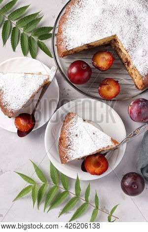 Homemade Plum Pie With Cut Pieces On Plates On A Light Background. Cake Is Sprinkled With Powdered S