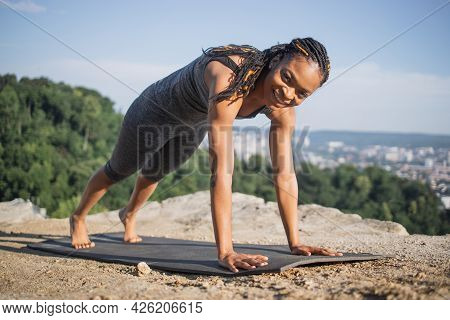 Beautiful Strong Woman With Black Skin Standing In Plank Position On Yoga Mat During Morning Exercis