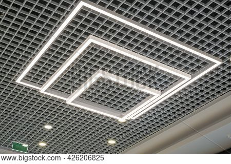 Suspended And Grid Ceiling With Halogen Spots Lamps And Drywall Construction In Empty Room In Store