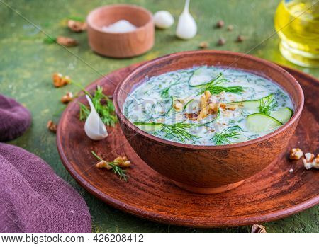Traditional Bulgarian Cold Soup Tarator With Cucumber, Herbs And Walnuts In A Brown Clay Bowl On A G