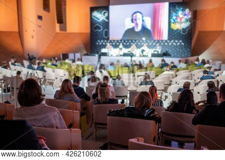 Unrecognizable male entrepreneur listening to online speaker while participating in business seminar in spacious modern auditorium