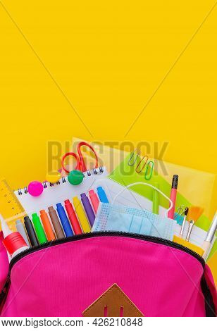 Back To School. Backpack For School With Bright Colorful Office Supplies And Medical Mask On Yellow