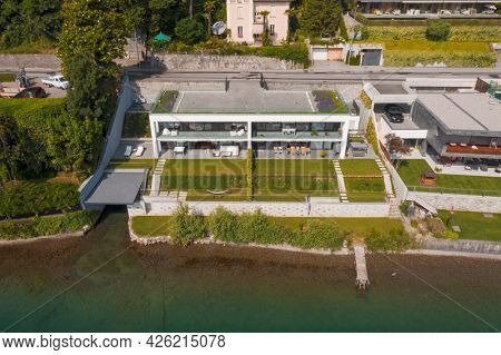Modern house with direct access to the lake. Aerial drone view from the lake of the house and the landscape surrounding the house.