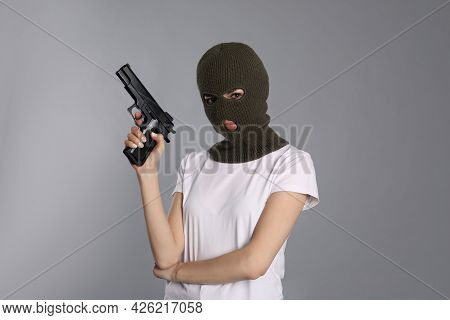 Woman Wearing Knitted Balaclava With Gun On Grey Background