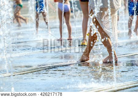 A Barefoot Young Woman In A White Dress Escapes The Heat In Splashes Of Water In A City Fountain.
