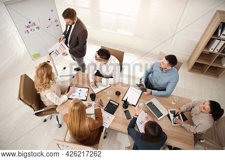 Businesspeople Having Meeting In Office, Above View. Management Consulting
