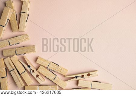Many Wooden Clothespins On Light Pink Background, Flat Lay. Space For Text