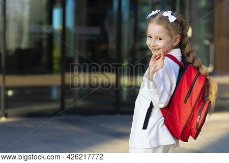 Little Cute Girl In Uniform Dress, Go To First Grade, Waving Hand. Happy Laughing Child Back To Scho