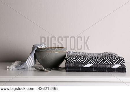 Kitchen Towels And Tableware On White Countertop Near Wall
