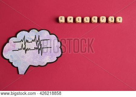 Human Brain Cutout With Pulse Lines Near Word Epilepsy Made Of Wooden Cubes On Crimson Background, F