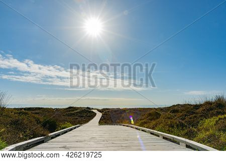 Long Wooden Walkway Through Coastal Vegetation Covered Dunes To Beach With Rising Sun Burst And Brig