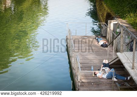 Ljubljana, Slovenia - June 15, 2021: Loves, Couples Of Young Adults, Lying Down On The Riverbank Of