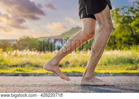 A Man Runner Is Engaged In Jogging On The Asphalt Without Shoes, Without Sneakers, For Health