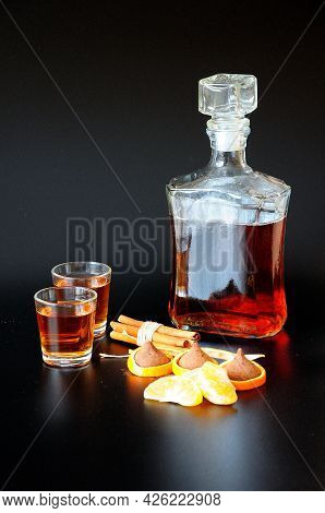A Bottle Of Cognac On A Black Background, Next To Two Glasses Of A Drink, Cinnamon Sticks, Tangerine