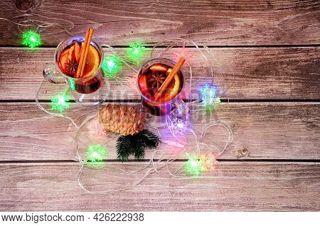 Christmas Garland, Two Hot Glasses With Spices And A Pine Cone On A Wooden Table.