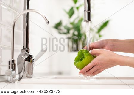 Wash Before Eat: Woman Washing Carefully Vegetable Fresh Pepper In Water In Kitchen Sink Before Cook