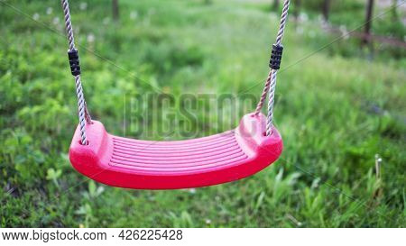 Lonely Swing Hanging In A Garden Full Of Green Grass And Trees In Springtime