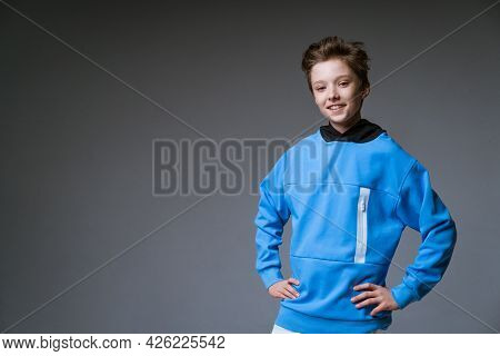 Portrait Of A Cute Guy Of European Appearance With A Snow-white Toothy Smile In A Blue Sweatshirt Po