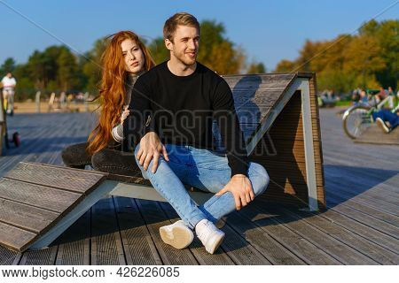 Happy Couple A Guy And A Girl With Long Red Hair Are Sitting On A Wooden Deck In An Embrace. Young M