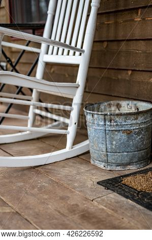 Cigarette Ash Bucket Sitting On A Wooden Porch In A Rural Setting With A Rocking Chair