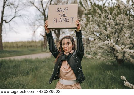Positive Millennial Nature-friendly Woman Posing. Recycling Concept. Eco-activist Female Holding Pla